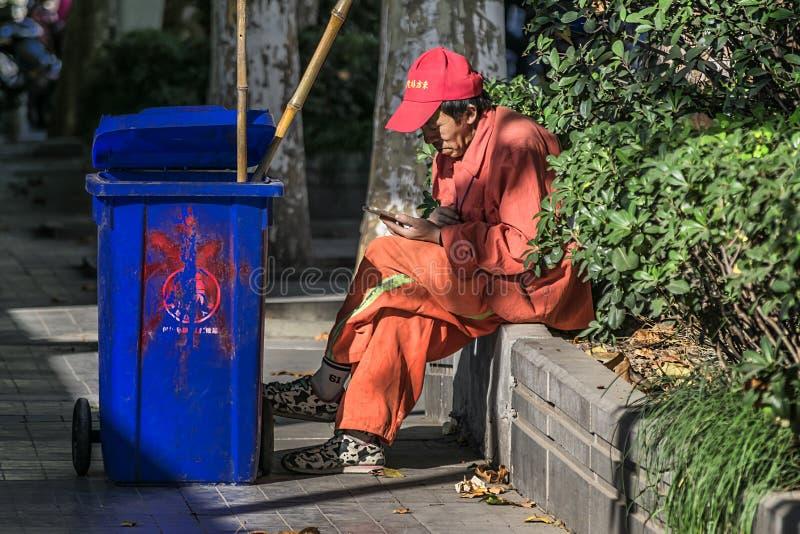 Travailleur d'hygiène regardant le téléphone portable sur la rue images libres de droits