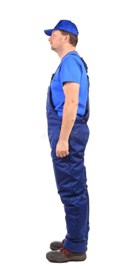 Travailleur dans des combinaisons bleues. Vue de côté. photographie stock libre de droits