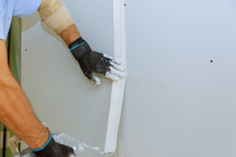 Travailleur dans des combinaisons plâtrant un mur avec le mastic de finissage utilisant un couteau de mastic Réparez le concept d image libre de droits