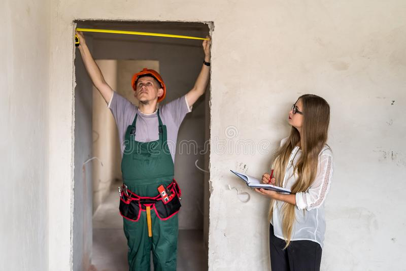 Travailleur dans l'écriture de mesure de porte et de femme d'uniforme en bloc-notes photos libres de droits