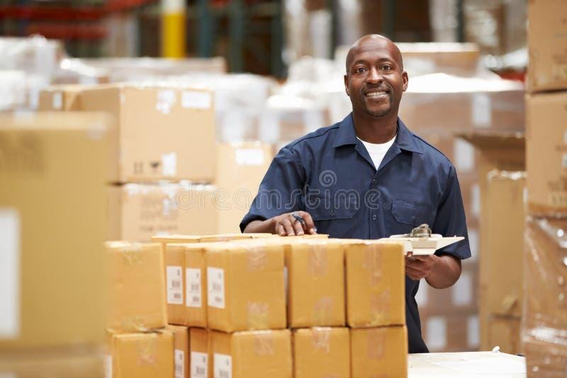Travailleur dans l'entrepôt préparant des marchandises pour l'expédition photos libres de droits
