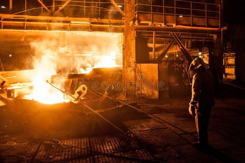 Travailleur dans l'industrie sidérurgique en versant le titane liquide du four à arc électrique photographie stock libre de droits