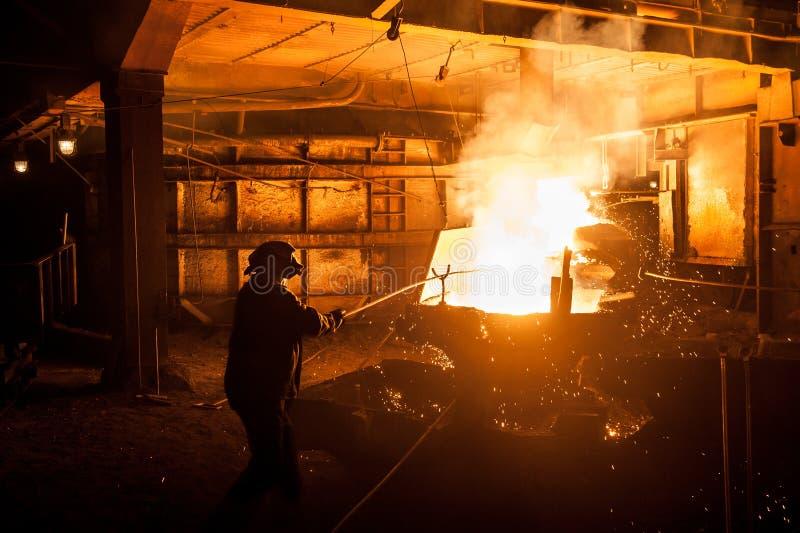 Travailleur dans l'industrie sidérurgique en versant les scories titaniques liquides du four à arc électrique images stock