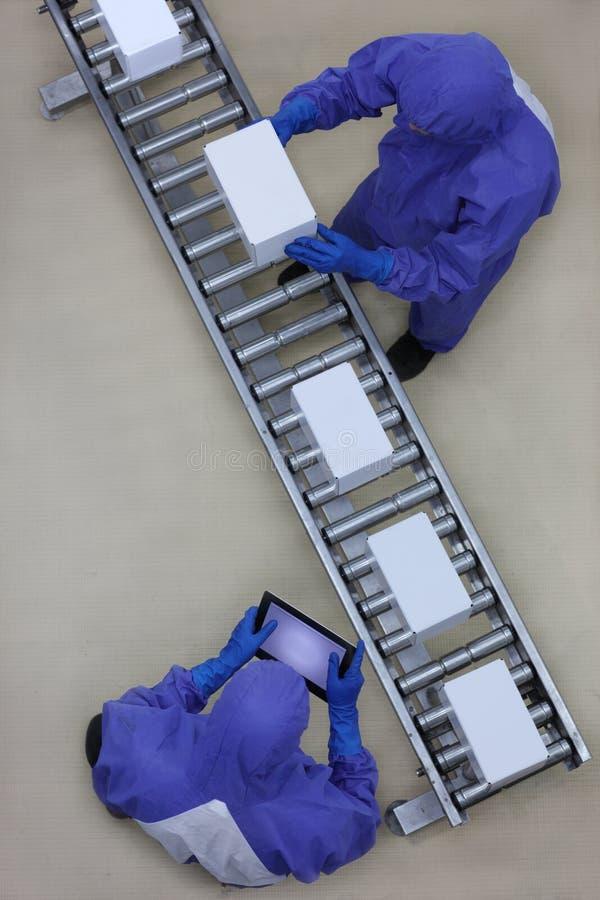 Travailleur dans l'uniforme bleu fonctionnant avec des boîtes sur la chaîne d'emballage photo libre de droits