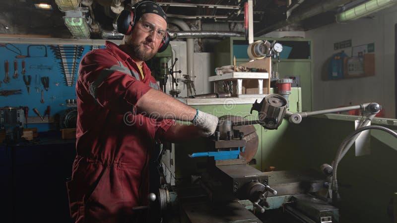 Travailleur dans l'uniforme rouge fonctionnant dans le tour manuel dans le grand atelier en métal photographie stock