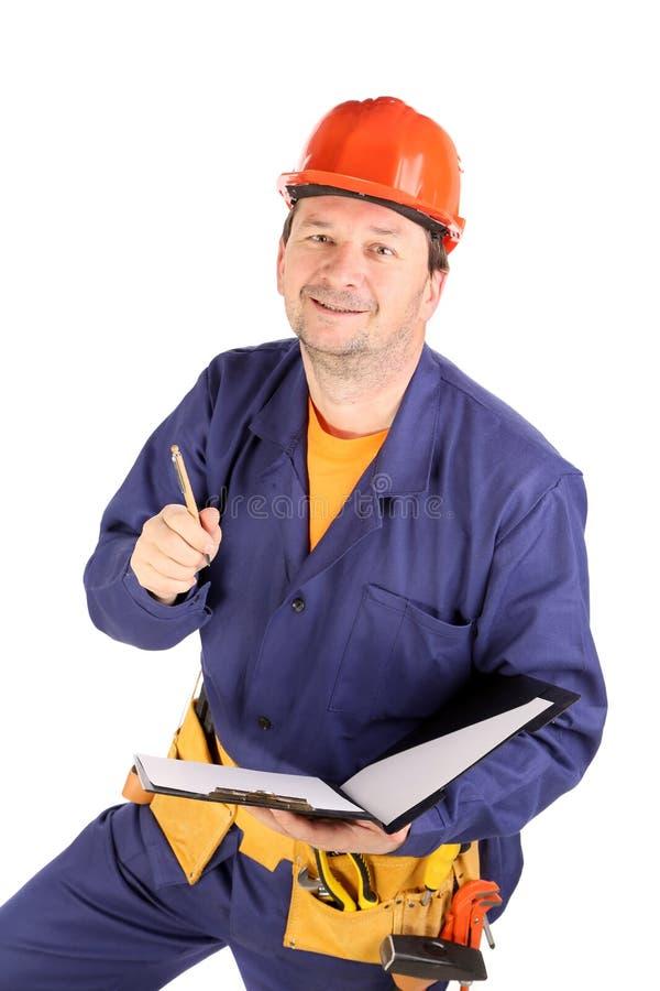 Travailleur dans le casque antichoc avec le stylo. image libre de droits