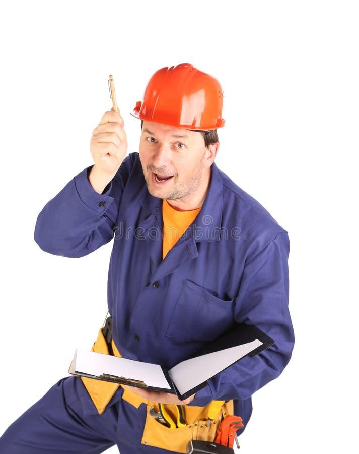 Travailleur dans le casque antichoc avec le stylo image stock