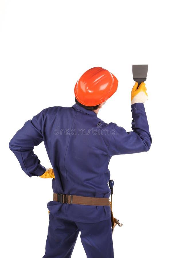 Travailleur dans le casque antichoc fonctionnant avec la scie à chantourner images libres de droits
