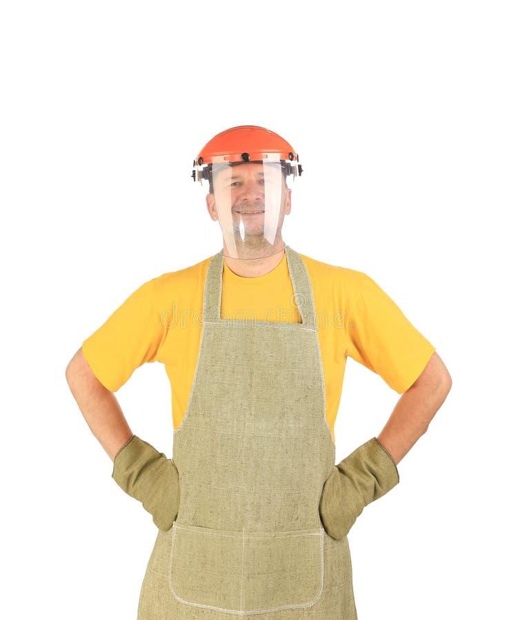 Travailleur dans le masque de tablier et de plastique photographie stock