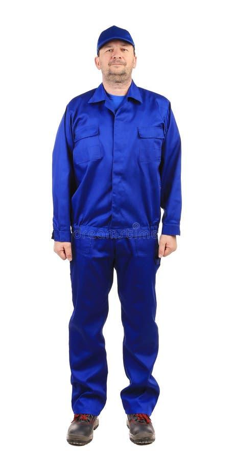 Travailleur dans les vêtements de travail bleus. photo stock