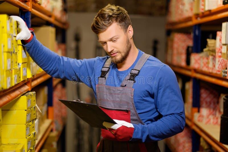 Travailleur dans un entrepôt de pièces de rechange photographie stock libre de droits