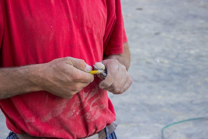 Travailleur de bâtiment affilant un crayon avec un couteau photos stock