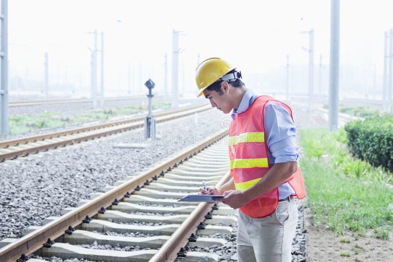 Travailleur de chemin de fer dans l'usage protecteur de travail vérifiant les voies ferrées images stock