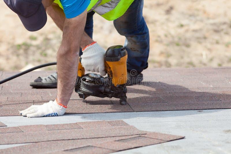 Travailleur de constructeur de Roofer avec le nailgun installant Asphalt Shingles ou des tuiles de bitume sur une nouvelle maison photo stock