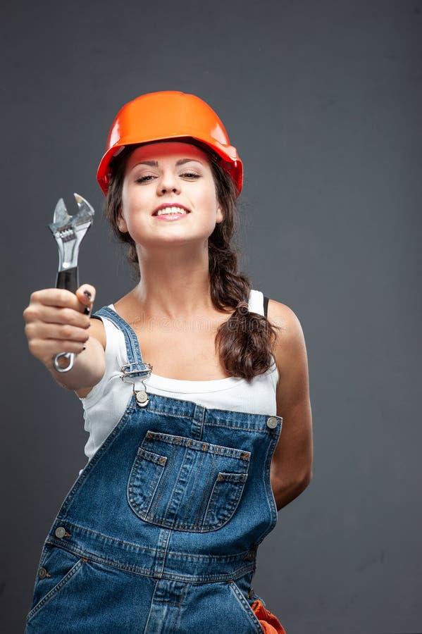 Travailleur de constructeur de femme avec la position de clé sur le fond gris images libres de droits