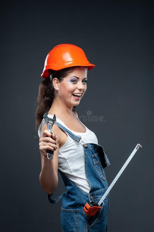 Travailleur de constructeur de femme avec la position de clé sur le fond gris photo libre de droits