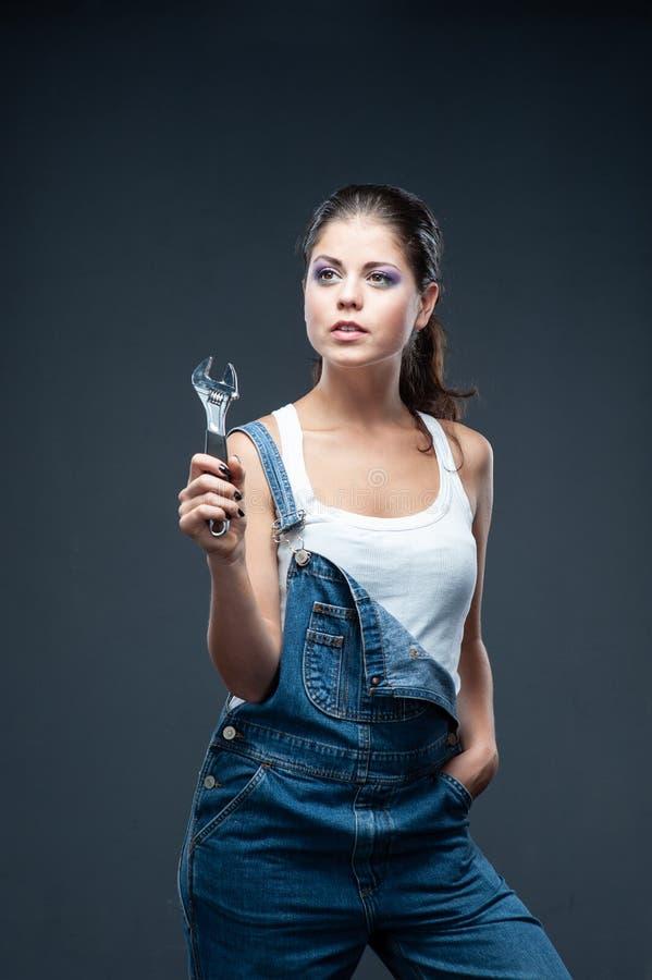 Travailleur de constructeur de femme avec la position de clé sur le fond gris photos stock