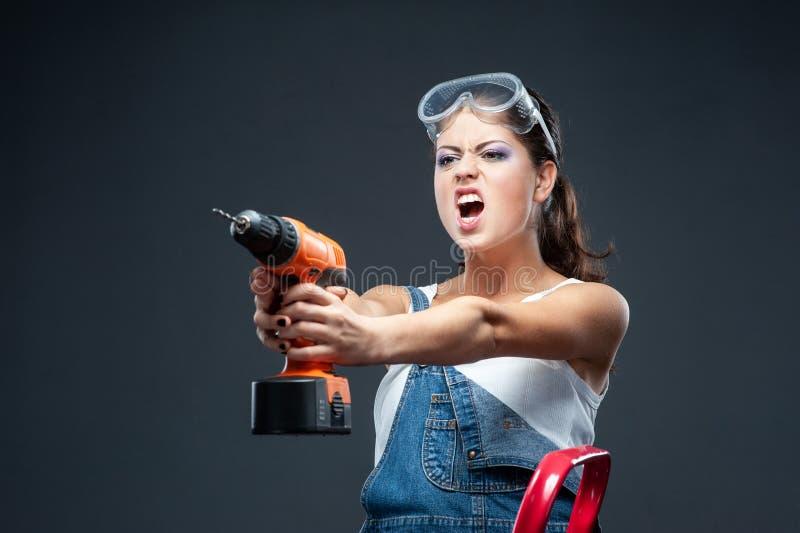 Travailleur de constructeur de femme avec la position de perceuse sur le fond gris images libres de droits