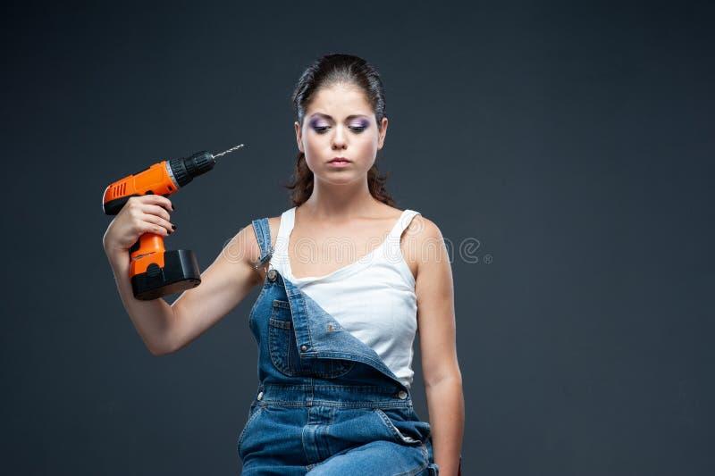 Travailleur de constructeur de femme avec la position de perceuse sur le fond gris photos stock