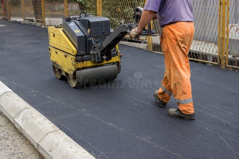 Travailleur de construction de routes derrière le rouleau de construction  photographie stock libre de droits