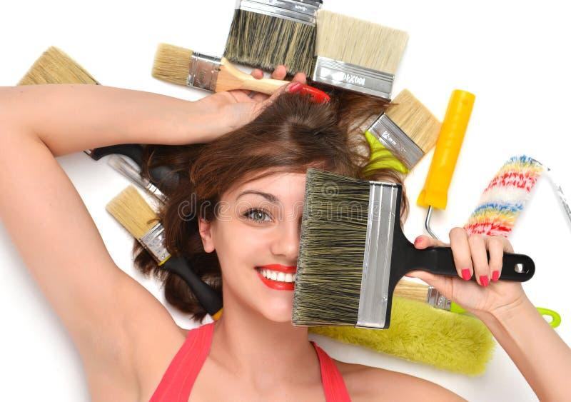 Travailleur de contructor de femme se trouvant sur un plancher avec la peinture de construction photo stock