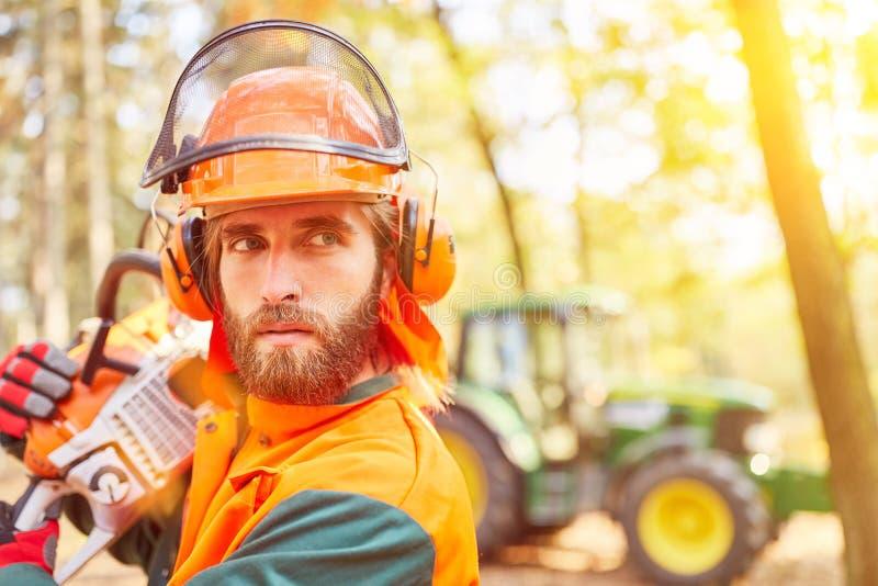 Travailleur de forêt avec la tronçonneuse et la sécurité photographie stock libre de droits