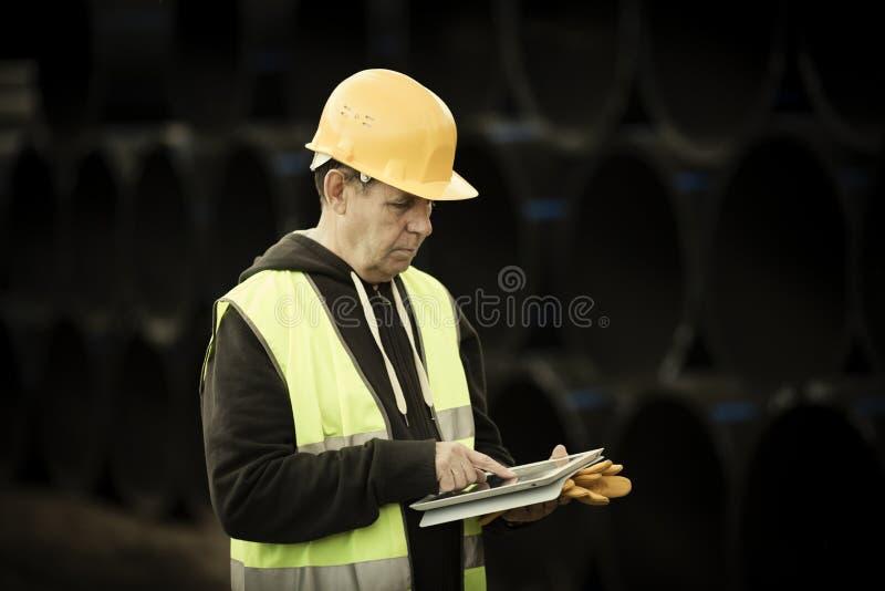 Travailleur de la construction à l'aide de la tablette digitale photographie stock