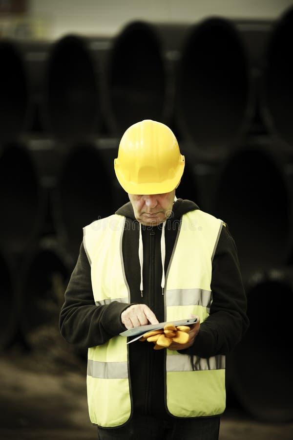 Travailleur de la construction à l'aide du comprimé numérique photos stock