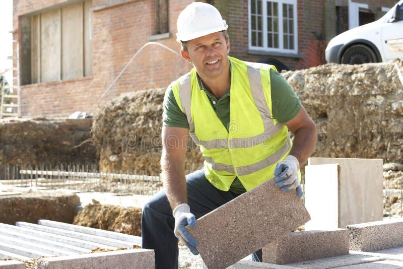 Travailleur de la construction étendant des parpaings images libres de droits