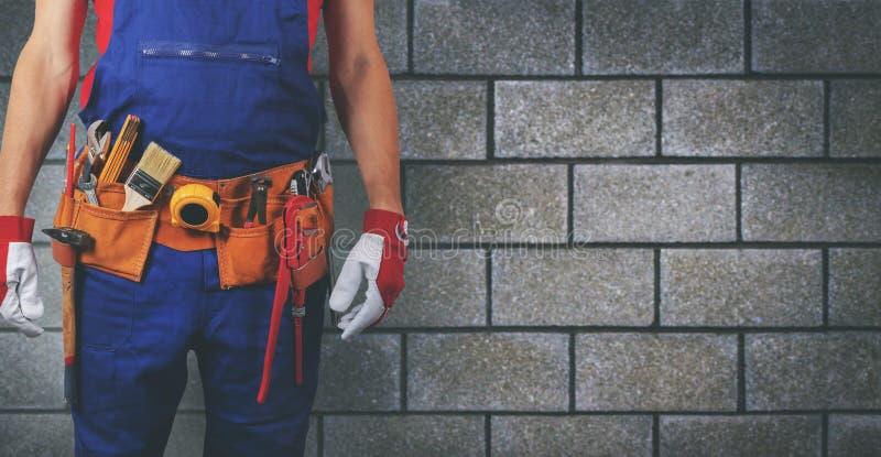 Travailleur de la construction avec la ceinture d'outil sur le fond de mur de bloc photos libres de droits