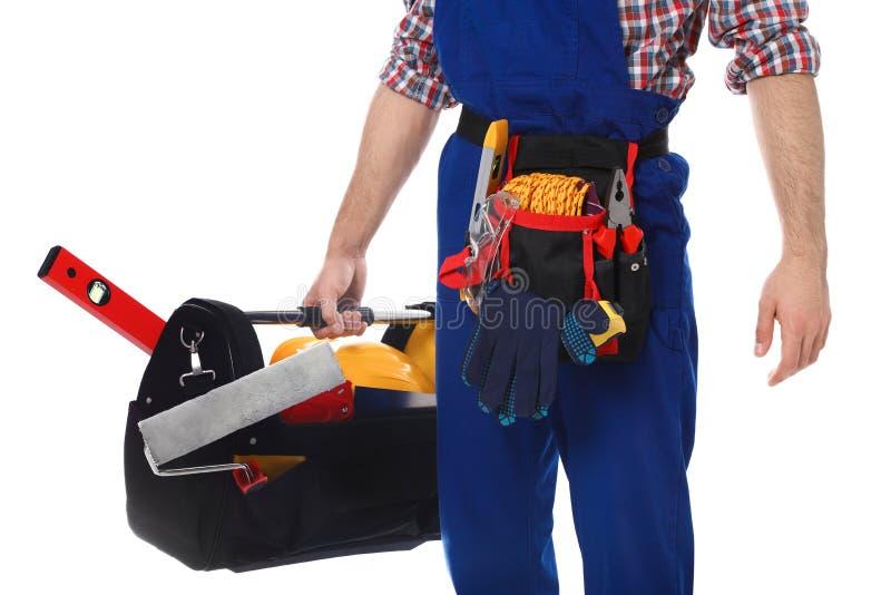 Travailleur de la construction avec l'ensemble d'outils sur le fond blanc, image stock