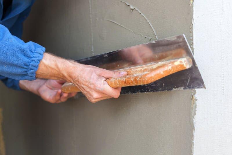 Travailleur de la construction avec la longue truelle plâtrant un mur photographie stock libre de droits