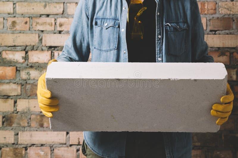 Travailleur de la construction avec le bloc photo stock