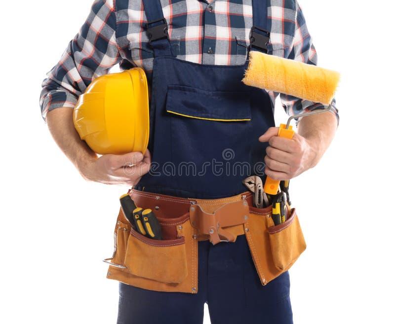 Travailleur de la construction avec le casque antichoc, le rouleau de peinture et la ceinture d'outil sur le fond blanc image stock