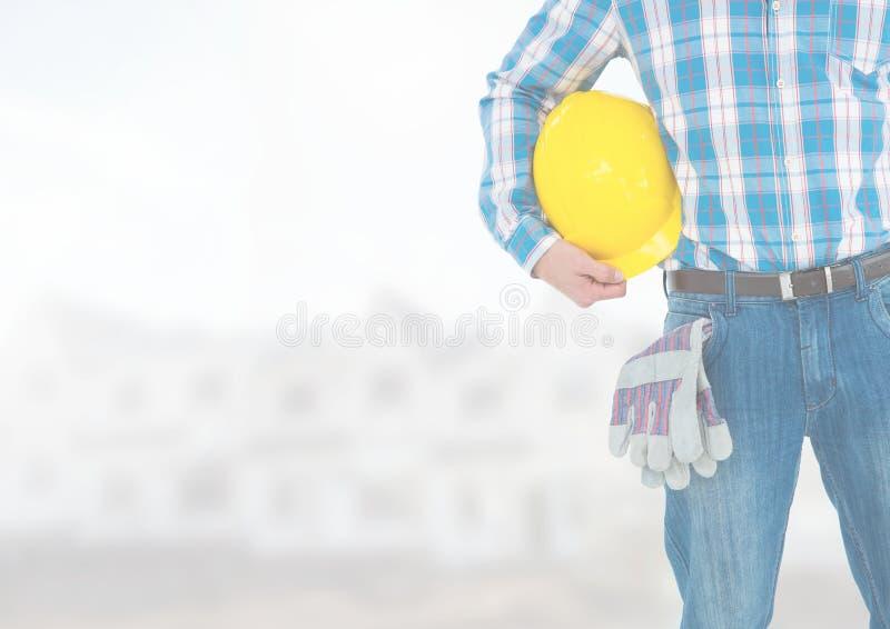 Travailleur de la construction avec le casque de sécurité devant le chantier de construction photo stock