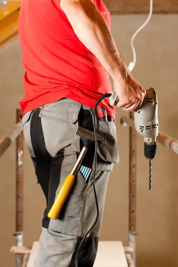 Travailleur de la construction avec le foret de main photo libre de droits