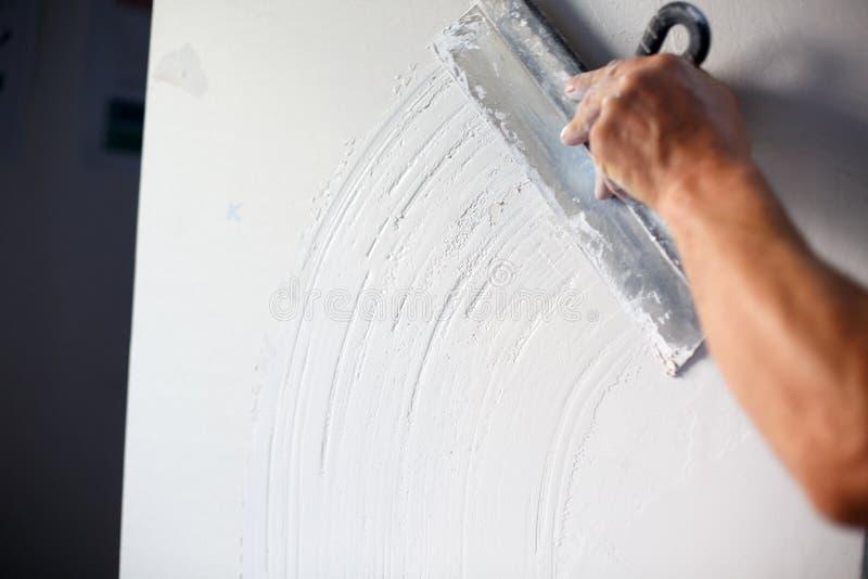 Travailleur de la construction avec la longue truelle plâtrant un mur images stock