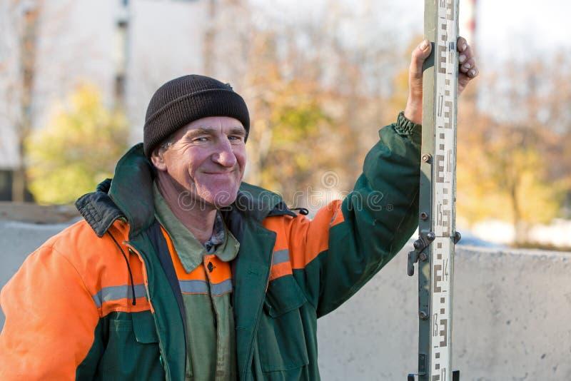 Travailleur de la construction avec niveler la tige photographie stock