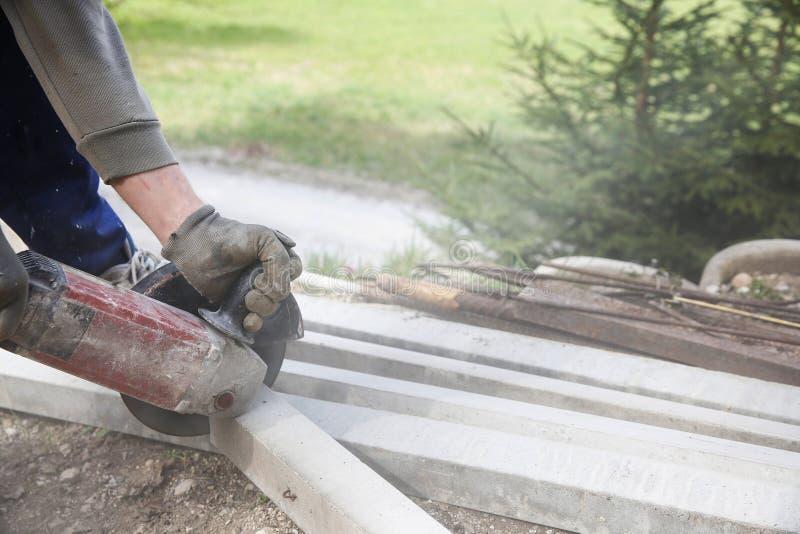 Travailleur de la construction coupant un pilier concret renforcé images stock