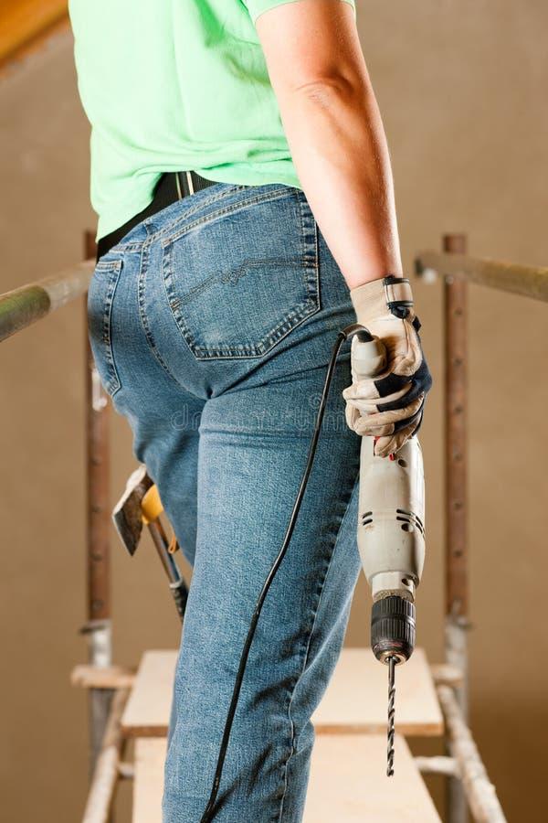 Travailleur de la construction de femme avec le foret de main images libres de droits