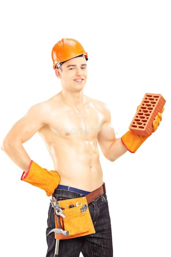 Travailleur de la construction de sexe masculin sans chemise avec le casque tenant la brique photographie stock