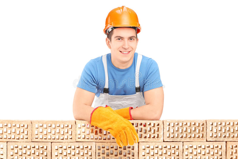 Travailleur de la construction de sexe masculin se reposant sur un mur de briques photo libre de droits