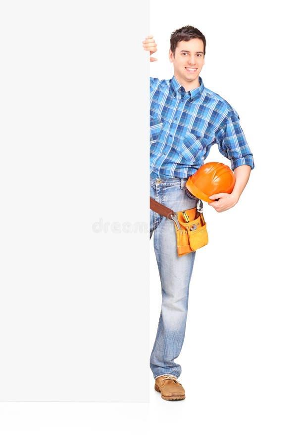 Travailleur de la construction de sexe masculin se tenant derrière le panneau photo libre de droits