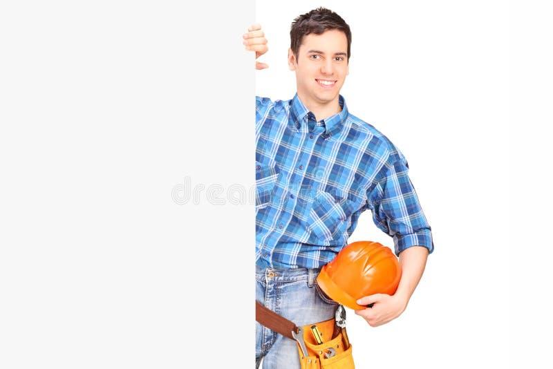Travailleur de la construction de sexe masculin se tenant derrière le panneau vide photo libre de droits