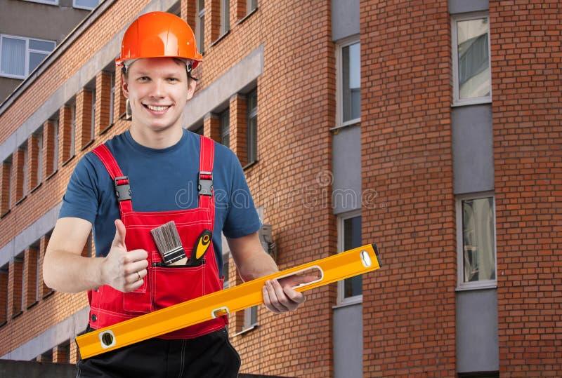 Travailleur de la construction de sourire amical montrant des pouces  image stock