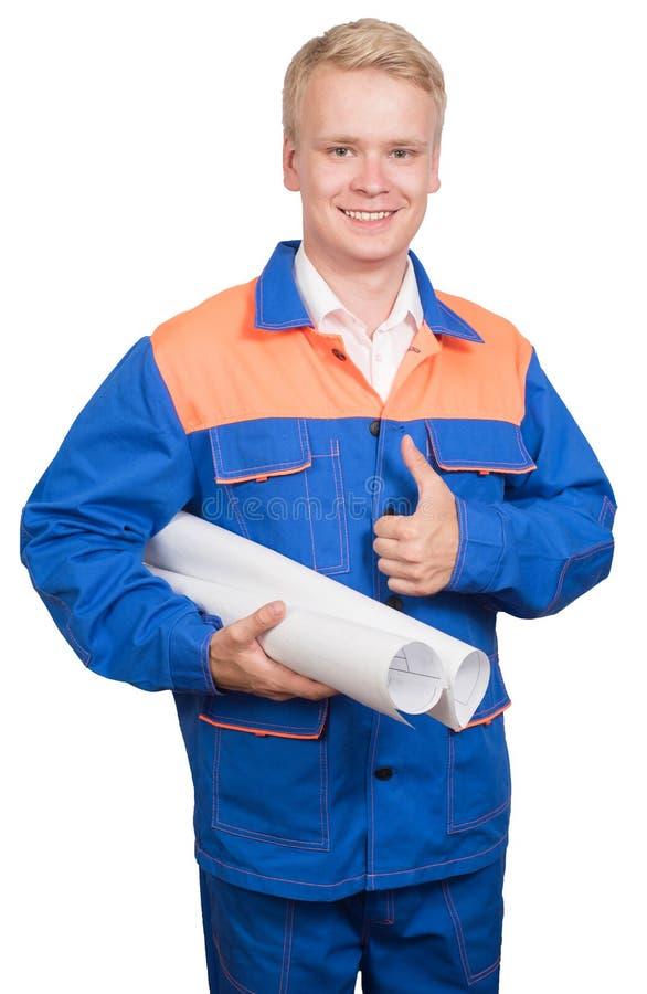 Travailleur de la construction de sourire dans un uniforme bleu avec le plan, pouce, d'isolement sur le fond blanc photos libres de droits