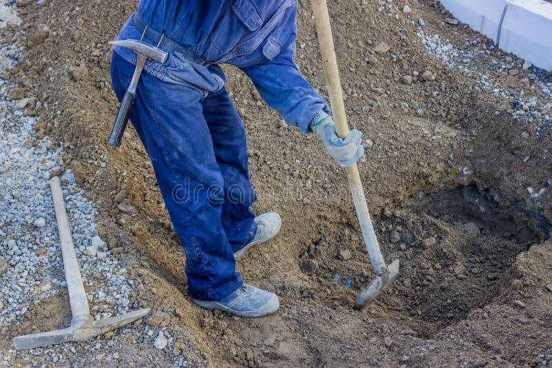Travailleur de la construction Digging qu'un trou souterrain profond avec poussent photo stock