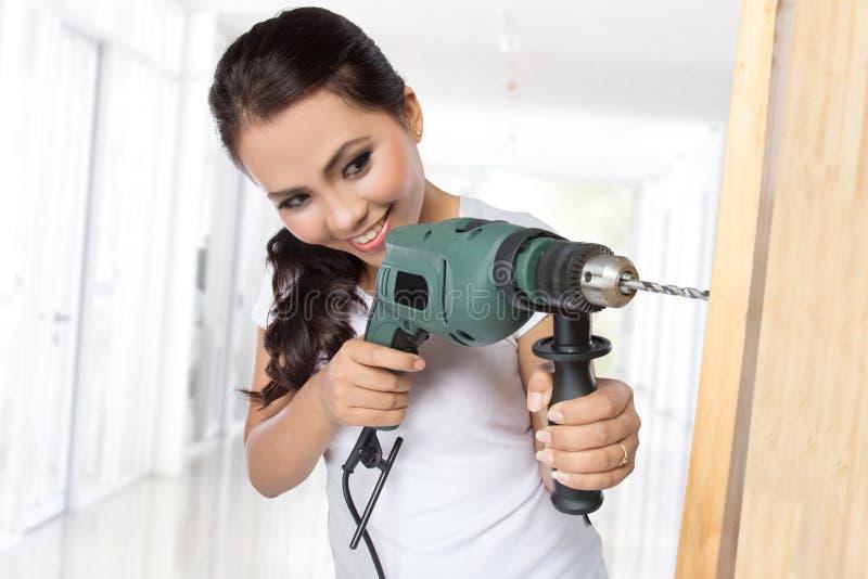 Travailleur de la construction féminin avec le foret photographie stock
