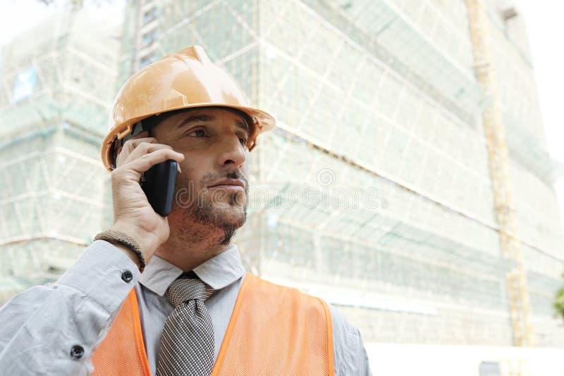 Travailleur de la construction faisant l'appel téléphonique photos libres de droits