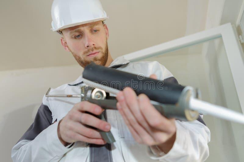 Travailleur de la construction installant la fen?tre dans la maison image stock